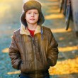 Sunlight Boy homeless bum in brown jacket and a fur hat and crum — Stock Photo