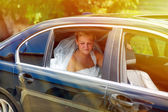 Sunlight blonde bride at a wedding sitting in a car — Stock Photo