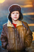 Zonlicht jongen in bruine jas en bont hoed op straat op blauwe abstr — Stockfoto