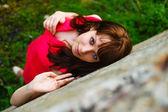 Fille brune yeux bleus dans une robe rouge sur le dessus du fond vert — Photo