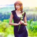Brunette thin sunlight portrait woman holding flowers on green o — Stock Photo #25090575