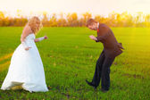Bride and groom sunlight dancing merrily in green field, couple, — Stock Photo