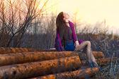 ブルネットの日光の女の子座りをする女性の外グループ木材 p で — ストック写真