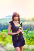 Brunette thin sunlight woman holding flowers on green open field — Stock Photo
