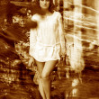 Retro sepia photo curly-haired girl with bare legs in a white sh — Stock Photo #25112759