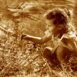 Royalty-Free Stock Photo: Retro sepia photo, little baby girl studying touching look yello
