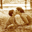 Retro sepia photo, Mom son of woman and child sitting on gra - Stockfoto