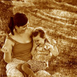 Retro sepia photo, mother, daughter, woman and child sitting gra - 图库照片