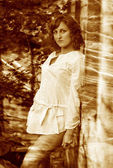 Retro sepia photo curly-haired girl with bare legs in white shir — Stock Photo