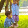 Children boy and girl sitting on green grass playing throwing le — ストック写真