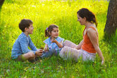 Boy and girl woman mom son daughter children are sitting on — Stock Photo