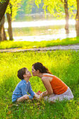 Mom and son woman child sitting on grass kissing sunset Roma — Stock Photo