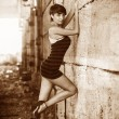 Retro sepia beautiful brunette woman sexy girl standing on a cit — Stock Photo