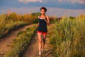 Beautiful healthy runs young brunette a woman athlete running ou — Stok fotoğraf