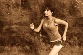 Beautiful healthy young brunette woman athlete running outdoors, — Stock Photo