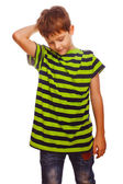 Blond boy kid in a striped green shirt is thinking, scratching h — Stock Photo