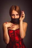 Woman girl in red corset, her mouth covered with bandage — Stock Photo