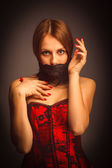 Woman girl in red corset, her mouth covered — Stock Photo