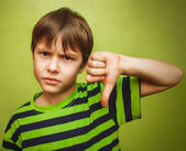 Baby boy teenager showing thumbs down on the big green backgroun — Stock Photo