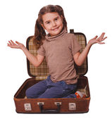 Baby girl brunette sitting in a suitcase for travel isolated on — Stock Photo