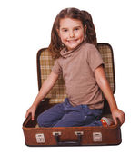 Girl brunette baby sitting in a suitcase for travel isolated on — Stock Photo