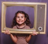 Teen girl child framed television smiling on gray background — Stock Photo