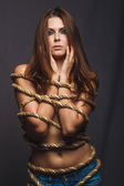 Brunette hostage, captive bound woman with rope prisoner in jean — Stock Photo