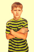 Angry restless evil dark blond kid in a striped green shirt, iso — Stock Photo