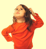 Portrait brunette kid in orange sweater, scratching his head thi — Stock Photo