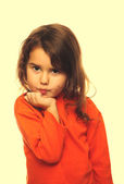 Portrait of curly brunette girl child orange sweater flirt flirt — Stock Photo