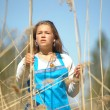 Girl in a blue sundress in a field of tall dry grass — Stock Photo #12522008