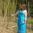 Girl in a blue sundress in a field of tall dry grass — Stock Photo #12522130