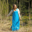 Girl in a blue sundress in a field of tall dry grass — Stock Photo