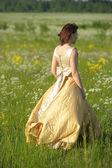Ung kvinna i en retro klänning i fältet — Stockfoto