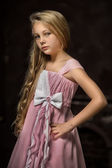 Beautiful young blonde girl with long hair in a pink princess dress. — Stock Photo