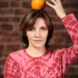 Portrait of young woman holding orange on her head — Stock Photo