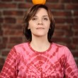 Portrait of young woman holding orange on her head — Stock Photo #14361061