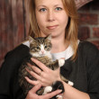 Young woman with a kitten in her arms — Stock Photo