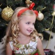 Cute little girl in front of a Christmas tree — Stock Photo