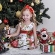 Cute little girl in front of a Christmas tree — Stok fotoğraf