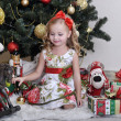 Cute little girl in front of a Christmas tree — Foto de Stock