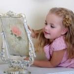 Beautiful little girl looking to retro mirror — Stock Photo #16871313
