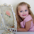 Beautiful little girl looking to retro mirror — Stock Photo