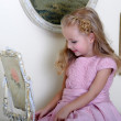 Beautiful little girl looking to retro mirror — Stock Photo #16871405