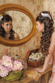 Beautiful young girl looking in the mirror — Stockfoto