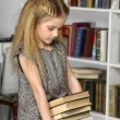 Girl with books in the library — Stock Photo