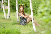 Woman wearing a crown of flowers next to a birch — Stock Photo
