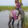 Young woman in a dress on a horse in water — Stock Photo #25818037