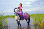 Young woman in a dress on a horse in water — Stock Photo