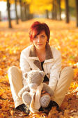 Woman in the autumn park with teddy bear — Stock Photo